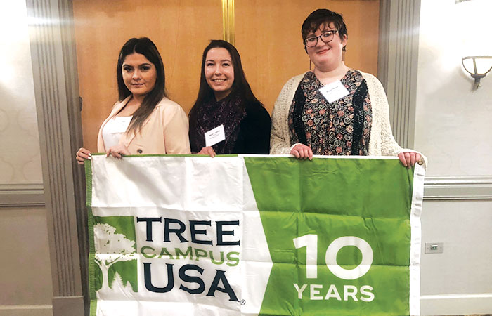 """Students Hold Tree Campus USA """"10 Years"""" Flag"""