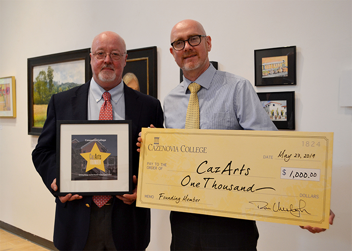 Cazenovia College Trustee, John McCabe, presented a check for $1,000 on behalf of the College to Shawn McGuire, Coordinator of CazArts Creative Alliance, at a reception in the Art Gallery of Reisman Hall