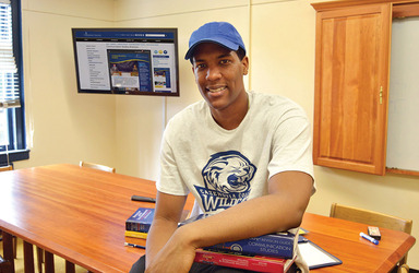 Male student smiling and wearing a Cazenovia Wildcats t-shirt