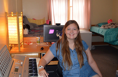 Female student sitting at a keyboard in her dorm room