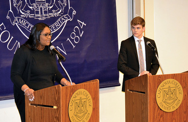 Two students standing at separate podiums debating a topic