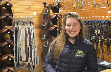 Female student smiling and standing in the Equine Education Center