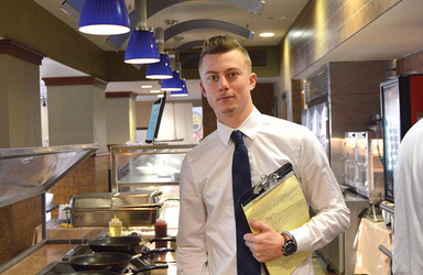 Professionally dressed male student with a clipboard at a catering event