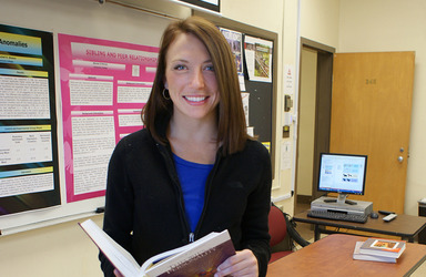 Female student standing in classroom holding a book