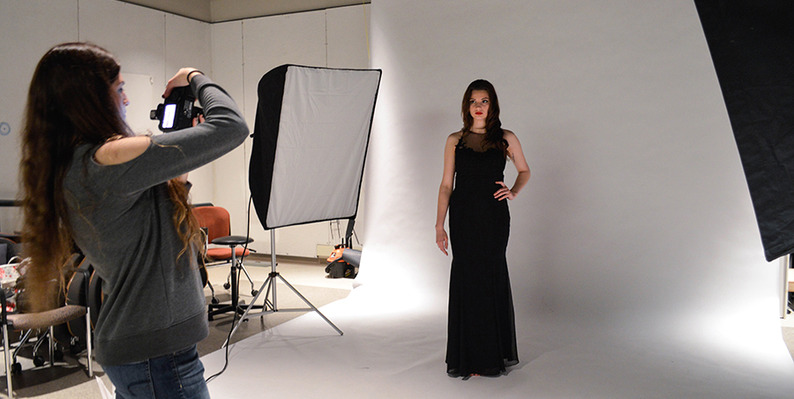 Student in the studio taking photographs of a model posing